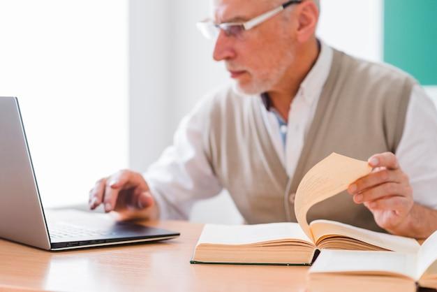 Profesor senior trabajando con laptop mientras sostiene la página del libro