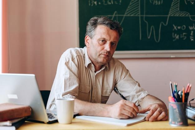 Profesor sentado en el aula con un bolígrafo y mirando a la cámara regreso a la escuela