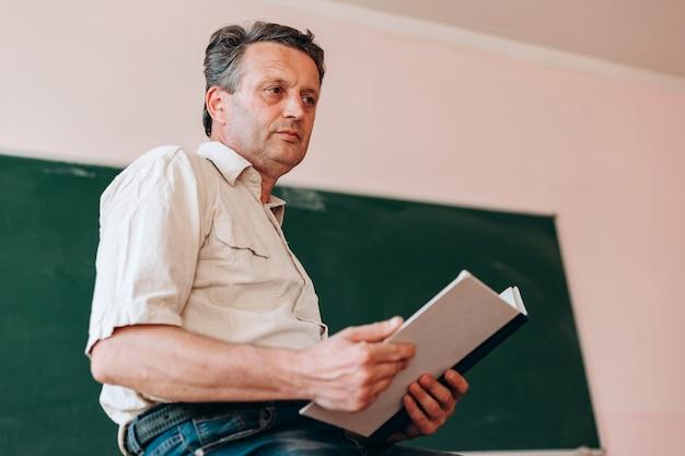 Profesor sentado con libro de texto abierto junto a una pizarra.