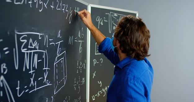 Profesor de sexo masculino caucásico en gafas y máscara médica escribiendo fórmulas y leyes matemáticas en clase. concepto de escuela. lección de matemáticas educativas. cerca del profesor de hombre girando a la cámara y mirando.