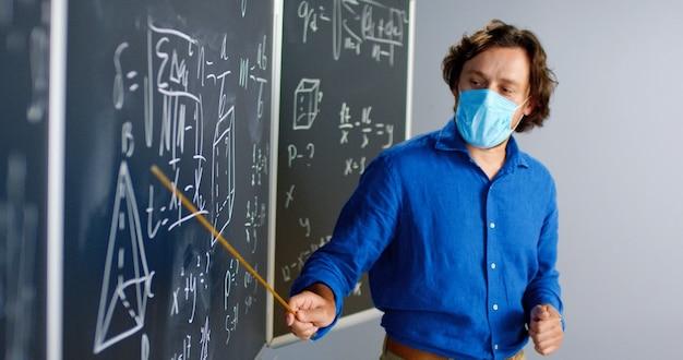 Profesor de sexo masculino caucásico en máscara médica de pie en el tablero en el aula y diciéndole leyes de física o geometría a la clase. concepto de pandemia. escuela durante coronavirus. lección de matemáticas educativas.