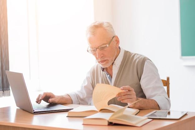 Profesor de sexo masculino envejecido que trabaja con el ordenador portátil mientras que lee el libro en sala de clase