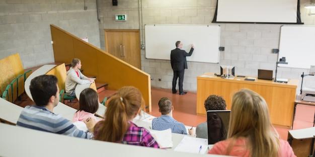 Profesor de sexo masculino con estudiantes en la sala de conferencias
