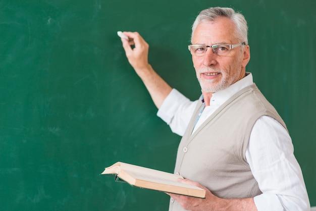 Profesor de sexo masculino mayor que sostiene el libro y que escribe en la pizarra