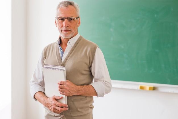 Profesor de sexo masculino mayor en los vidrios que sostienen el cuaderno que se opone a la pizarra