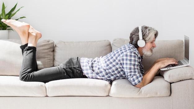 Profesor en el sofá usando laptop