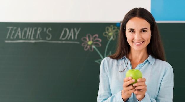 Profesor sonriente sosteniendo una manzana con espacio de copia