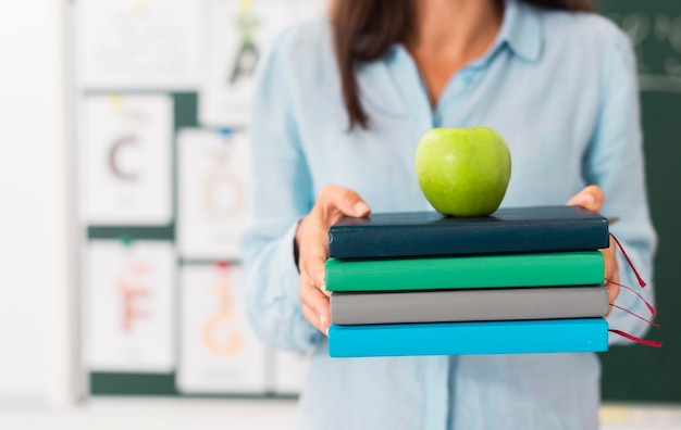 Profesor sonriente sosteniendo un montón de libros y una manzana