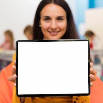 Profesor sonriente sosteniendo una tableta de pantalla vacía