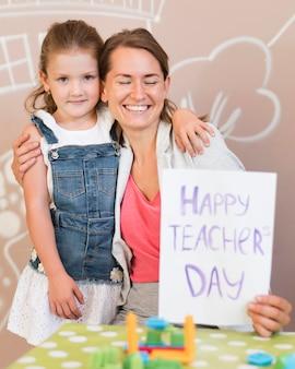 Profesor sonriente de tiro medio con niña