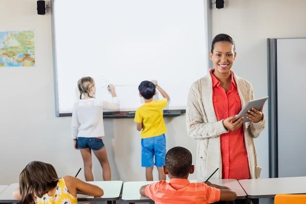 Profesor sonriente usando una tableta mientras los alumnos están trabajando