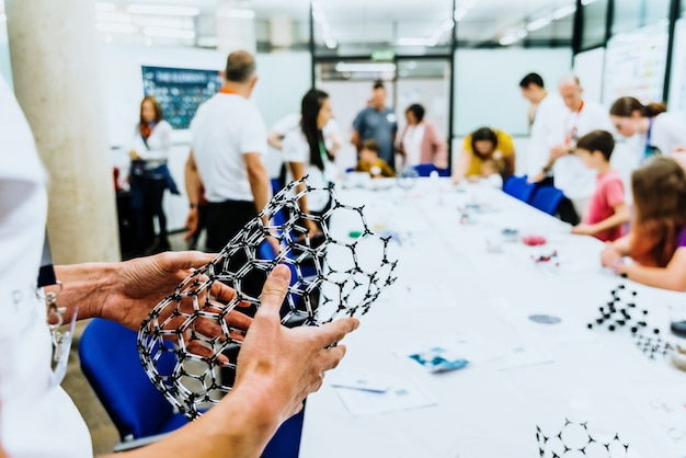 Profesor sosteniendo frente a sus estudiantes en la clase de biología un modelo molecular de un supermaterial de grafeno.