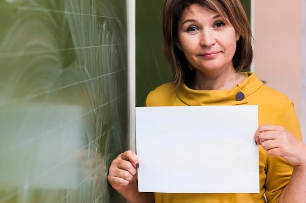 Profesor sosteniendo la hoja de papel en blanco