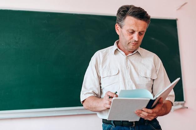 Profesor sosteniendo y leyendo el libro de texto de pie junto a una pizarra.