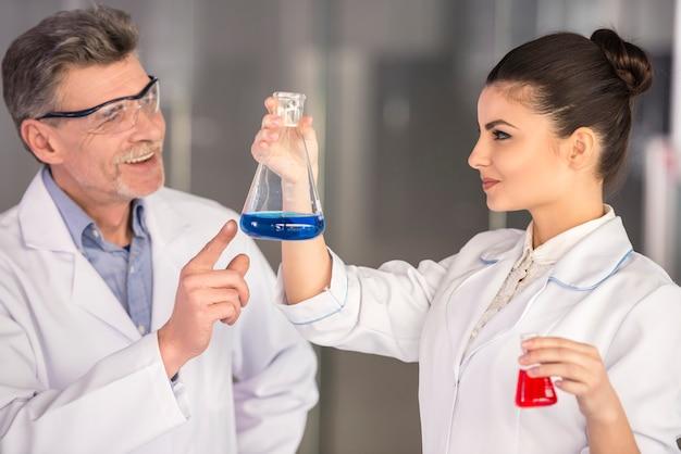 Profesor y su asistente trabajando en laboratorio.