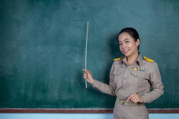 Profesor tailandés en traje oficial enseñando frente a la pizarra