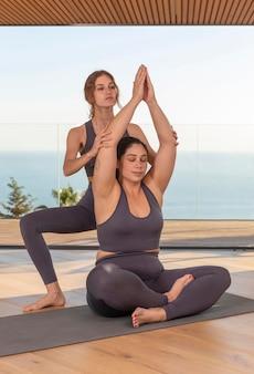 Profesor de tiro completo ayudando a mujer con pose
