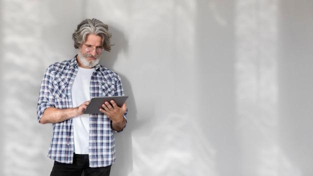 Profesor de tiro medio de pie y sosteniendo la tableta con espacio de copia