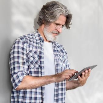 Profesor de tiro medio de pie y sosteniendo la tableta