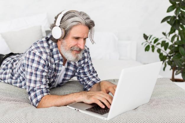 Profesor de tiro medio sentado en la cama usando una computadora portátil