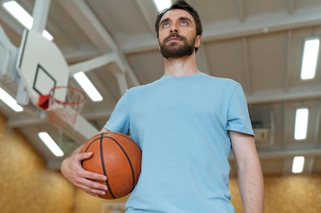 Profesor de tiro medio sosteniendo la pelota de baloncesto