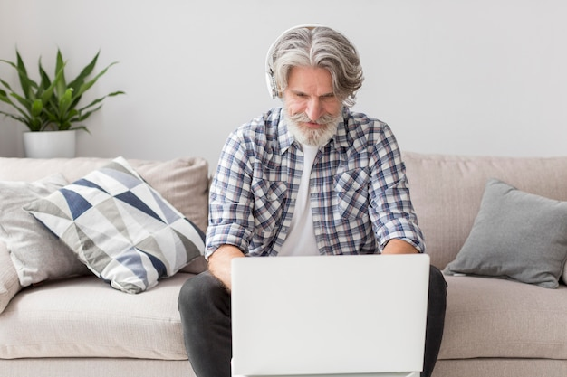 Profesor de tiro medio trabajando en la computadora portátil