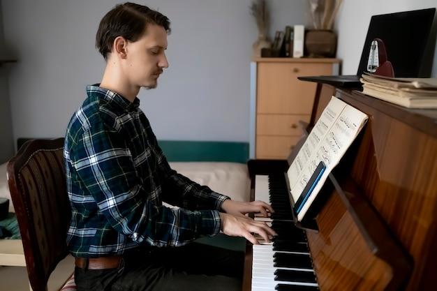 Profesor tocando el piano durante su lección en línea