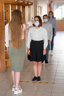 Profesor tomando la temperatura corporal en la escuela