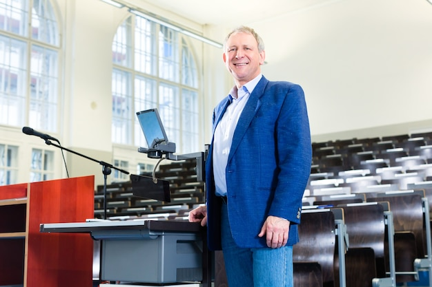 Profesor universitario dando conferencia y de pie en el escritorio