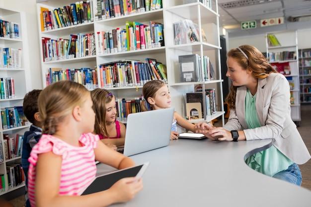 Profesor usando computadora con alumnos