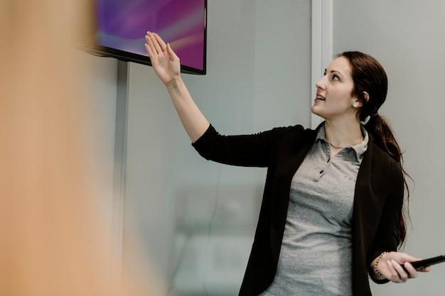 Profesor utilizando una pantalla de televisión en el aula.