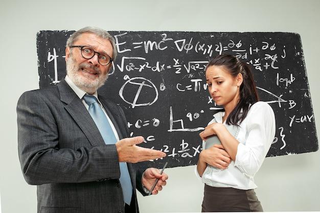 Profesor varón y mujer joven contra la pizarra en el aula