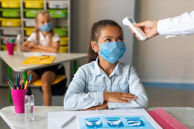 Profesor de vista frontal tomando la temperatura de un alumno