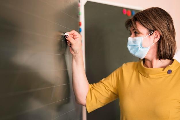 Profesor de vista lateral con máscara escribiendo en la pizarra