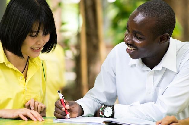Profesora africana que enseña a estudiantes asiáticos sobre lenguas extranjeras.