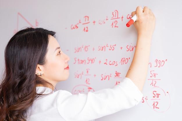 La profesora asiática está reescribiendo la conferencia en la pizarra