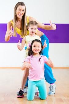 Profesora de baile dando clases de baile de zumba a los niños.