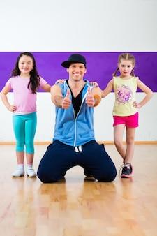 Profesora de baile dando clases de fitness zumba a los niños i