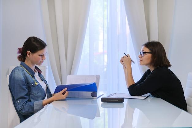 Profesora enseñando a una adolescente individualmente, lecciones privadas, ayuda con los exámenes