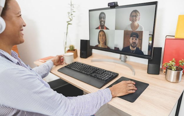 Profesora haciendo videollamadas con estudiantes desde casa - concepto de tecnología y distancia social - enfoque en la mano