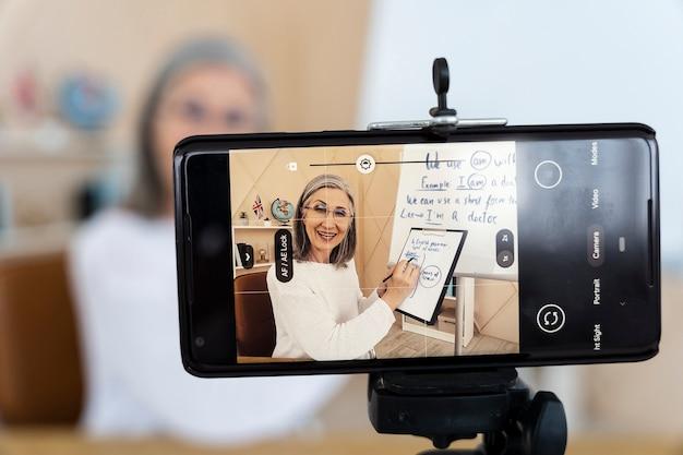 Profesora de inglés sonriente haciendo lecciones en línea en su teléfono inteligente