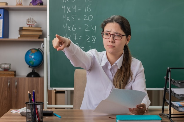 Profesora joven con gafas sentado en el escritorio de la escuela con páginas en blanco apuntando con el dedo índice a algo comprobando el trabajo a domicilio frente a la pizarra en el aula