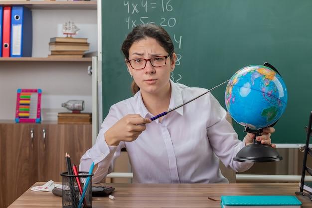 Profesora joven con gafas sosteniendo globo apuntando