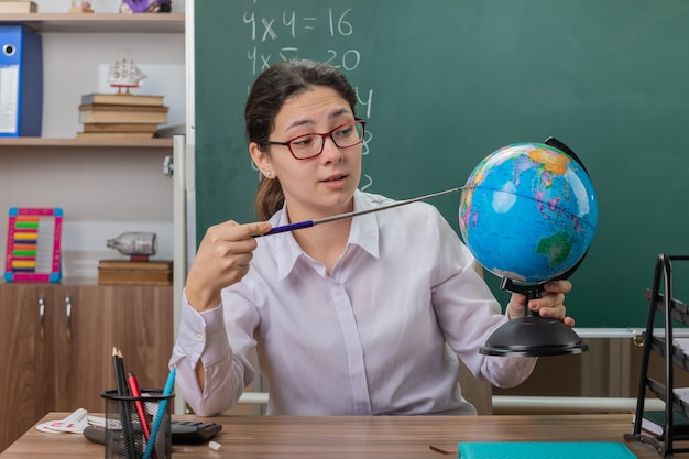 Profesora joven con gafas sosteniendo globo y puntero explicando la lección mirando confiado sentado en el escritorio de la escuela frente a la pizarra en el aula