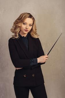 Profesora joven con puntero en mano cerca de una pared con textura gris.