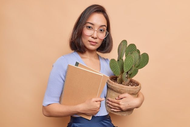 Profesora joven seria mira con confianza al frente lleva gafas ópticas puente azul sostiene dos blocs de notas y cactus en macetas aisladas sobre pared beige