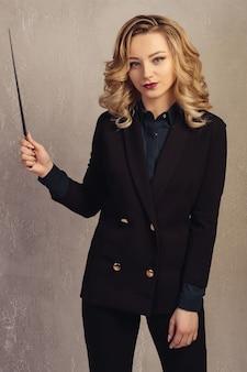 Profesora de mujer de negocios joven con puntero en mano cerca de una pared con textura gris.