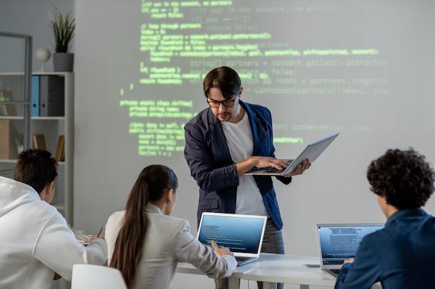Profesora con portátil de pie junto al escritorio e inclinándose sobre uno de los estudiantes mientras verifica la tarea o la consulta en la lección