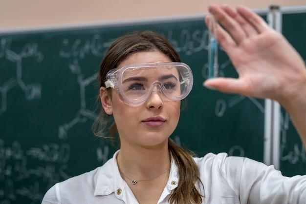 Profesora realizando un experimento con líquido en un matraz en la lección. la ciencia es interesante y fascinante