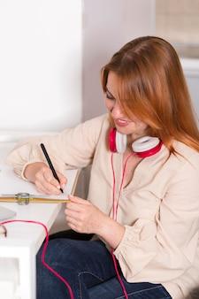 Profesora sonriente sosteniendo una clase en línea desde casa